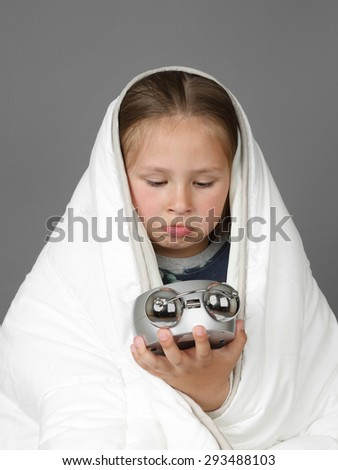 Little sleepless girl sits wrapped in blanket and look at alarm clock on gray background - stock photo