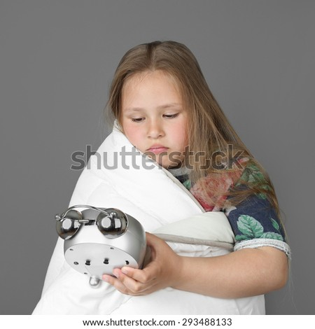 Little sleepless girl wrapped in blanket looks at alarm clock on gray background - stock photo