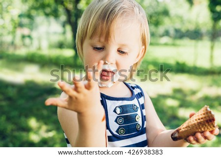 Little smeared girl looking at leaked hand with ice cream - stock photo
