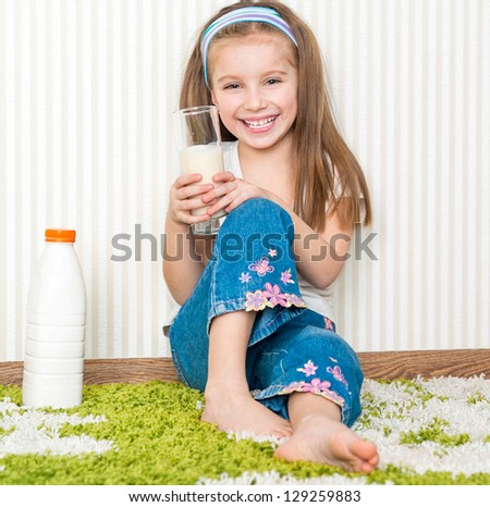 little smiley girl drink the milk  on the floor in her home - stock photo