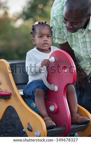 Little Smiling African American Girl Playing with Dad Outdoor - stock photo