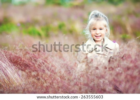 little smiling blond girl in the beige jacket in the field - stock photo