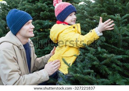 little smiling boy and his father shopping for christmas tree - stock photo