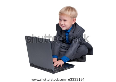 Little smiling boy dresses with gray suit and blue shirt sitting on the floor and browsing in the internet through computer (laptop) isolated on white background - stock photo