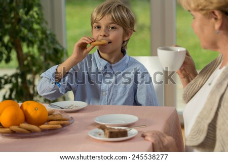 Little smiling boy eating his grandmother's delicious cake - stock photo