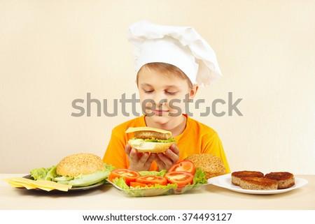 Little smiling boy in chefs hat preparing a hamburger - stock photo