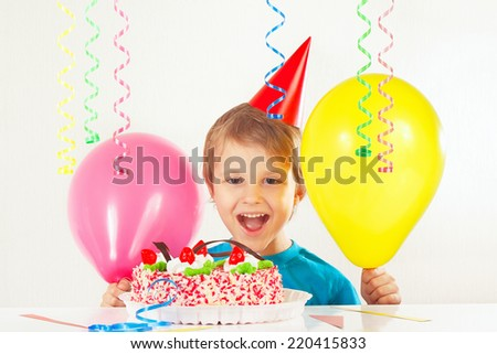 Little smiling boy in holiday cap with a birthday cake and balloons  - stock photo