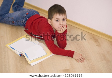 Little smiling boy is lying on a floor at home - stock photo