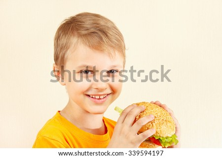 Little smiling boy with a tasty hamburger - stock photo