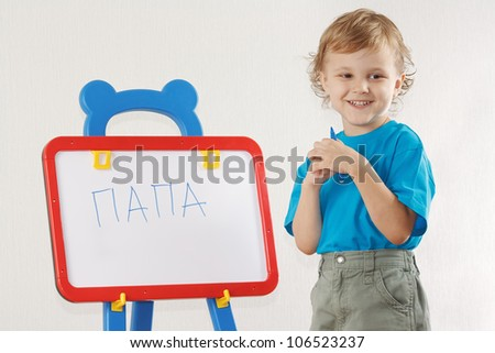 Little smiling boy wrote the word papa on whiteboard - stock photo