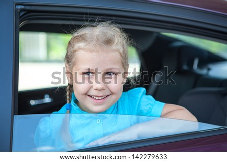 Little smiling Caucasian girl inside of back seat of car - stock photo