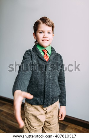 Little smiling child boy gesturing hand greeting or meeting handshake - stock photo