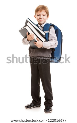Little smiling child boy with school backpack holding education books in hands - stock photo