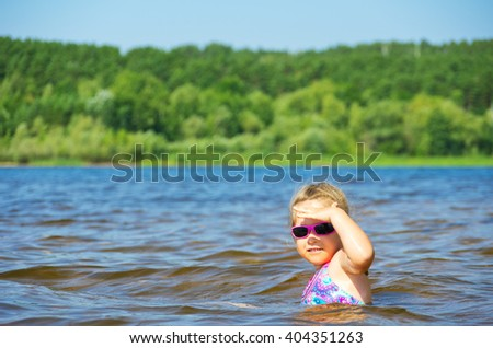 Little smiling girl at river - stock photo