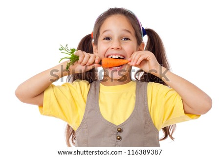 little smiling girl biting the carrot, isolated on white - stock photo