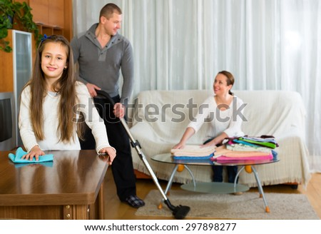 Little smiling girl helping parents to clean at home. Focus on girl - stock photo
