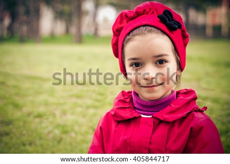Little smiling girl in red jacket and hat portrait with space for text. Toned photo - stock photo