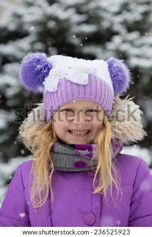 little smiling girl outdoors at the snowfall time  - stock photo