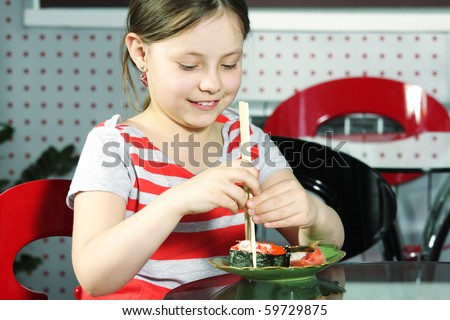 Little smiling girl trying to use sticks for sushi - stock photo