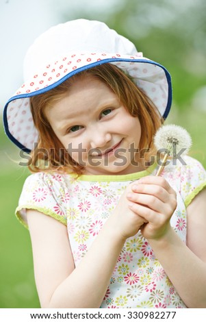 Little smiling girl with dandelion in her hands outdoors - stock photo