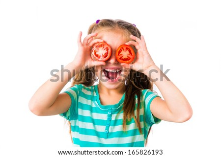 little smiling girl with tomatoes near the eye - stock photo