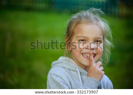 Little smiling pretty girl puts forefinger to his lips. - stock photo