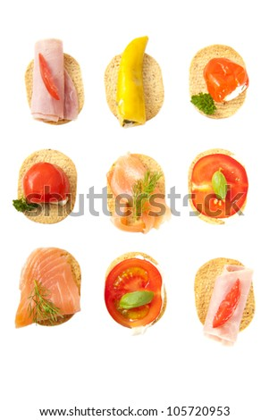 Little snacks with cheese vegetables meat and fish in a row over white - stock photo