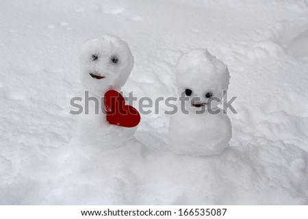 Little snowman offering a red heart to its lover girl - stock photo