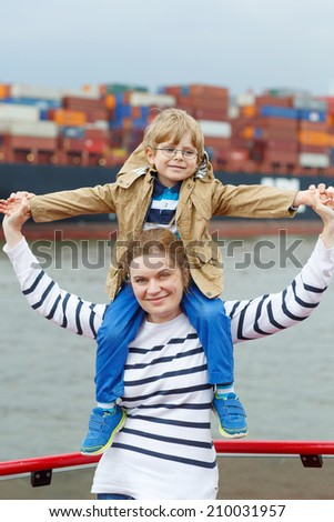 Little son and his mother watching ships on a ferry - stock photo