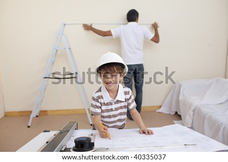 Little son drawing plans and father working in bedroom - stock photo