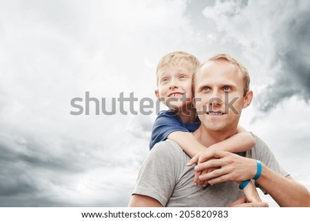 Little son hugs his father on neck with great cloudscape  - stock photo