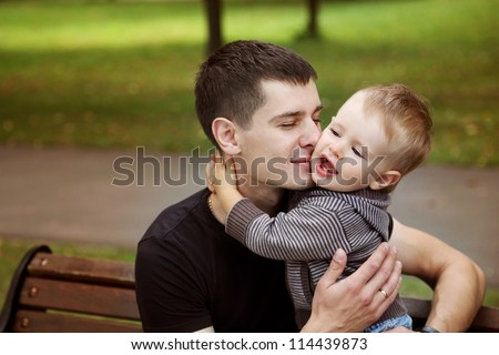 Little son kissing his father  in summer park - stock photo