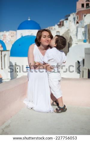 Little son kissing his mother (bride) on Santorini Island, Greece  - stock photo