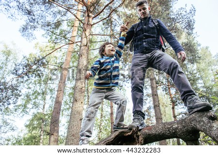 little son with father climbing on tree together in forest, lifestyle people concept, happy smiling family on summer vacations - stock photo