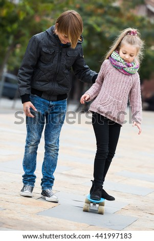 Little spanish girl learning to ride skateboard, teenage brother supporting her - stock photo