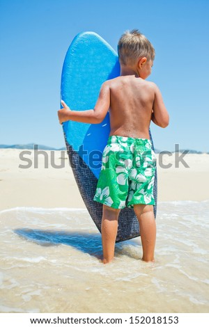 Little surfer. Back view of boy with surfboard standing near ocean. - stock photo