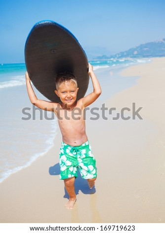 Little surfer. Boy with surfboard runing near ocean. - stock photo