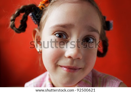 Little surprised girl with pigtails on an orange background - stock photo