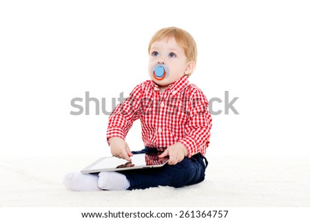 Little sweet child plays with computer tablet on a white background. Learning toys and early development. - stock photo