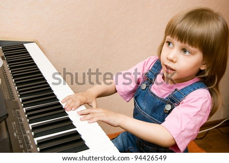 Little sweet girl plays piano - stock photo