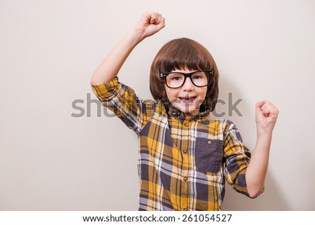 Little things can make him happy! Little boy in eyewear keeping arms raised and smiling while standing against grey background - stock photo
