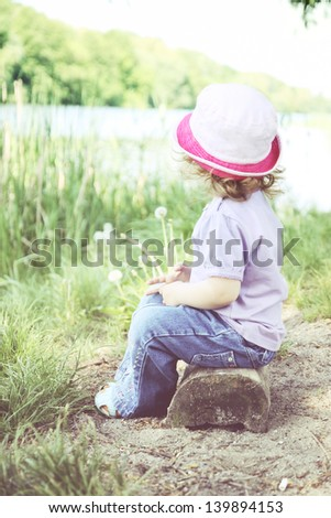 Little thoughtful girl sitting on the bank of the river - stock photo