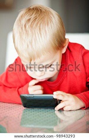 little three year old boy playing with his media player with a puzzled expression  shallow depth of field, focus on the eye - stock photo