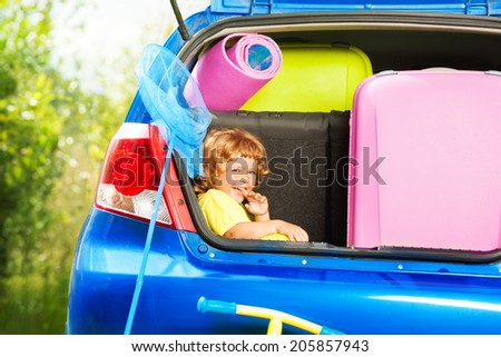 Little three years old boy sitting in the car trunk waiting for parents to put bags for the trip in the car - stock photo