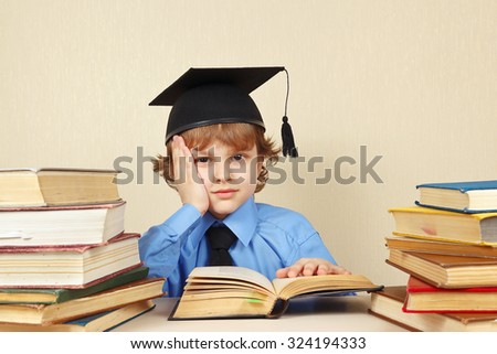 Little tired boy in academic hat studies an old books - stock photo