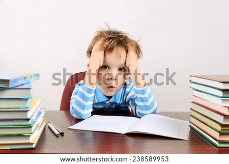 little tired boy sitting at a desk horizontal - stock photo