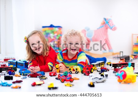 Little toddler boy and girl playing with model car collection on the floor. Transportation and rescue toys for children. Toy mess in child room. Many cars for little boys. Educational games for kids. - stock photo