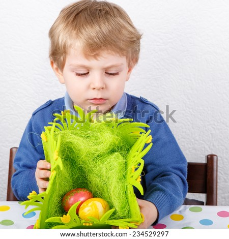 Little toddler boy being happy about Easter egg hunt, traditional action in Germany for Eastern holiday, Square format. - stock photo