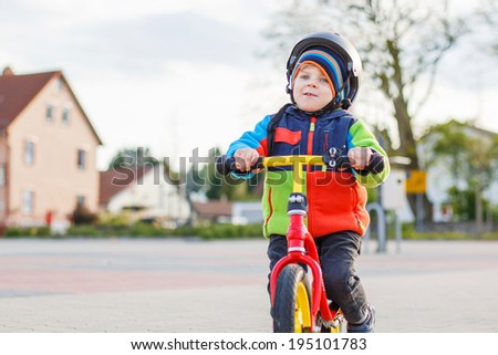 Little toddler boy having fun and riding his bike  in the city - stock photo