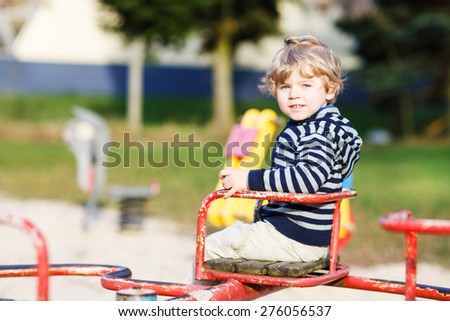 Little toddler boy having fun on old carousel on outdoor playground. - stock photo